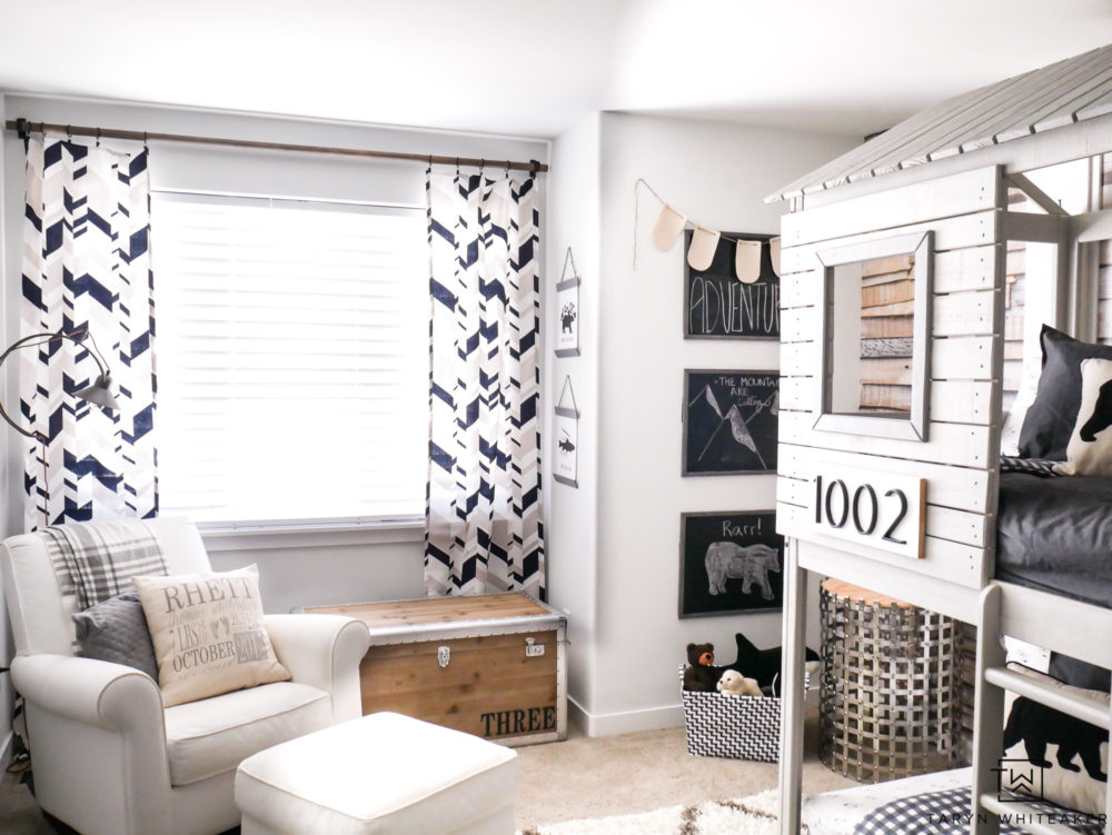 Neutral Boys room filled with cream, gray, and navy. Adorable geometric curtains mixed with plaid makes for a cute rustic modern space.