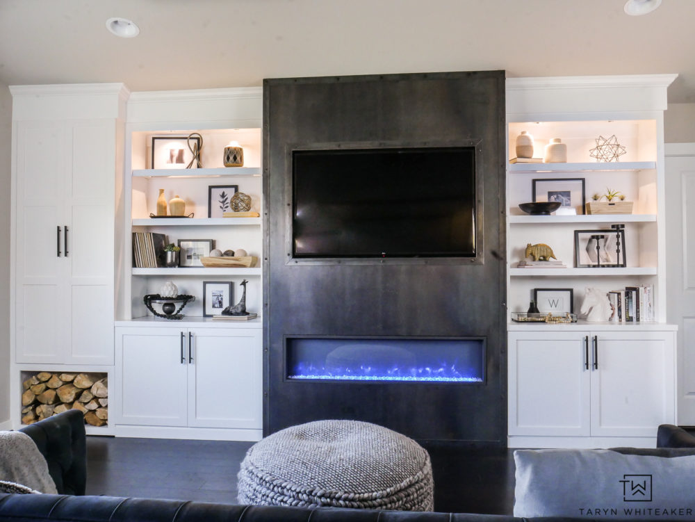 Gorgeous modern built ins with sleek steel fireplace and built in wood storage. Love the black and white decorative accessories.