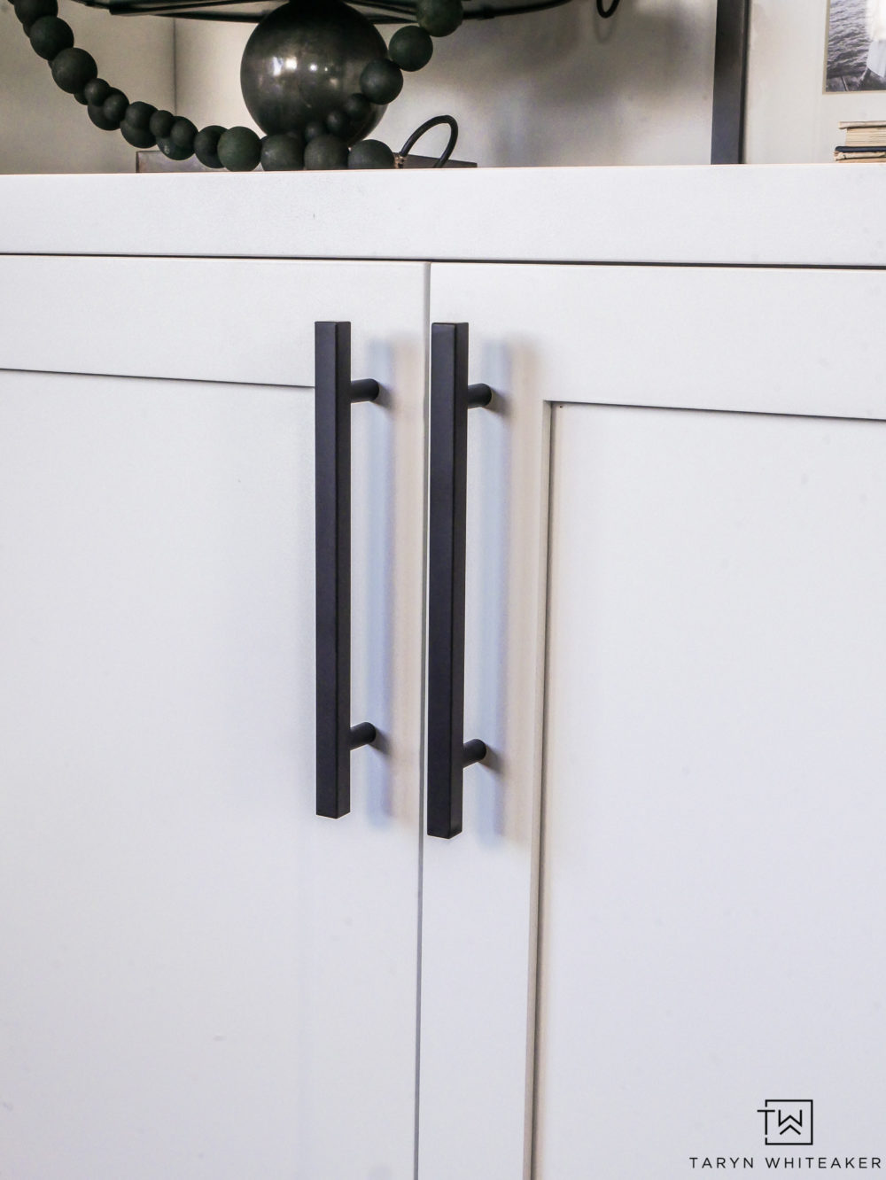 Sleek black hardware on white cabinets.