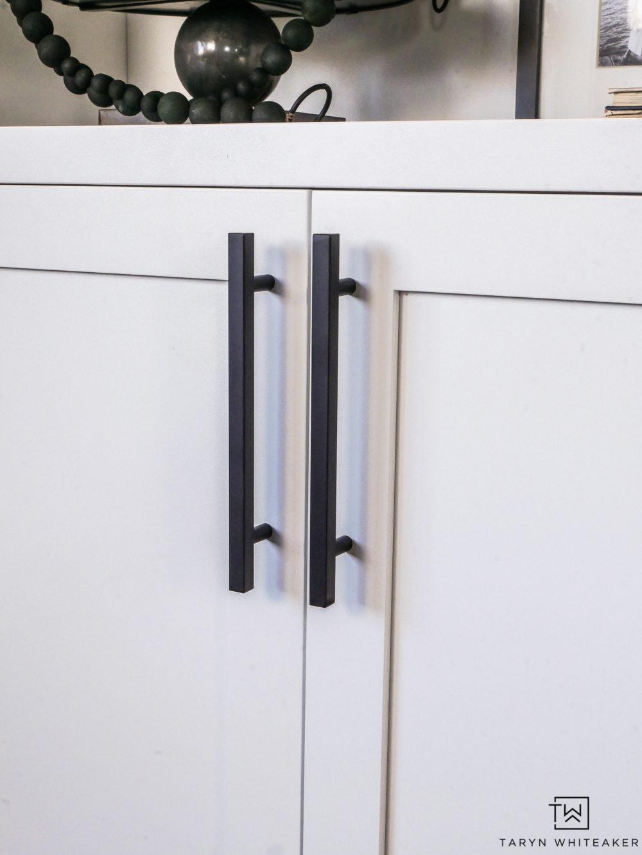 Sleek black hardware on white cabinets.