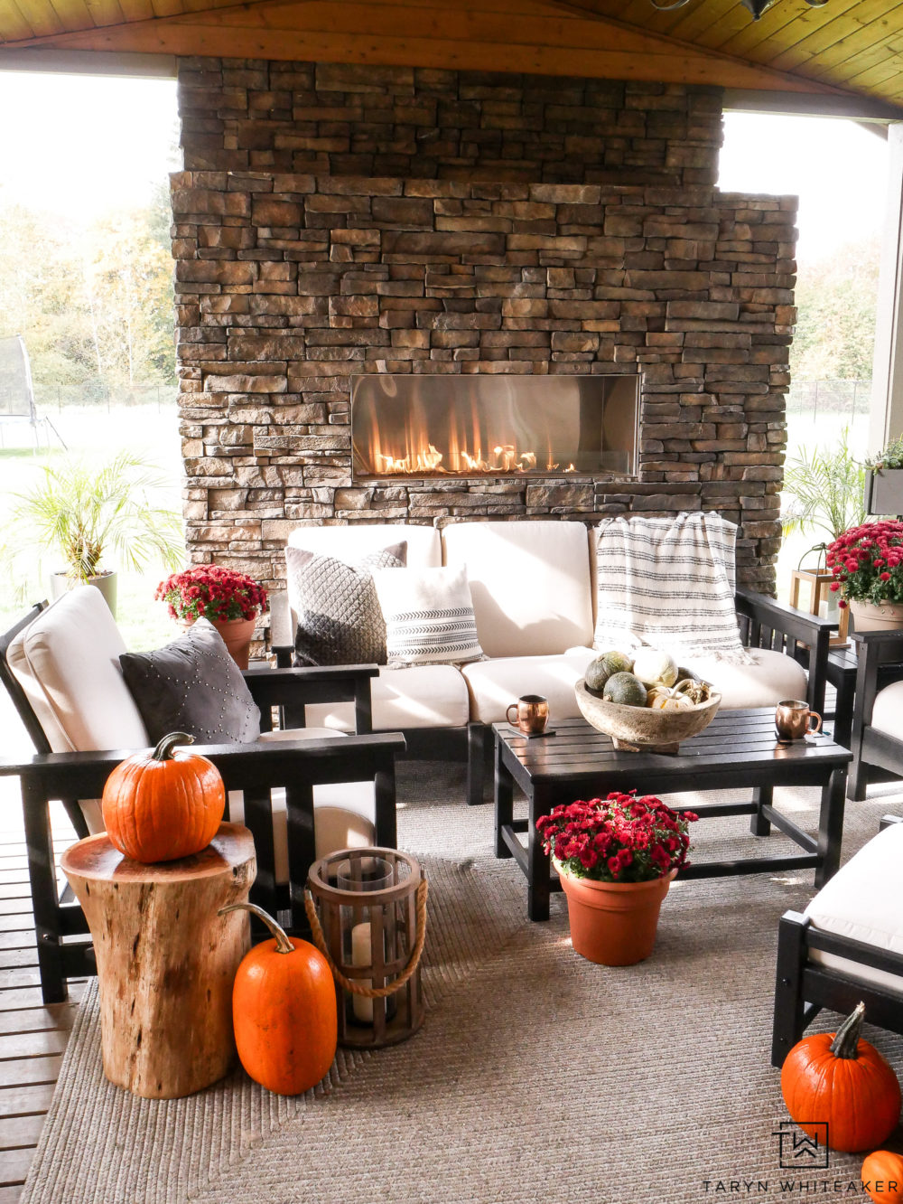 Beautiful outdoor living space all decorated for autumn with pops of orange pumpkins and red mums!