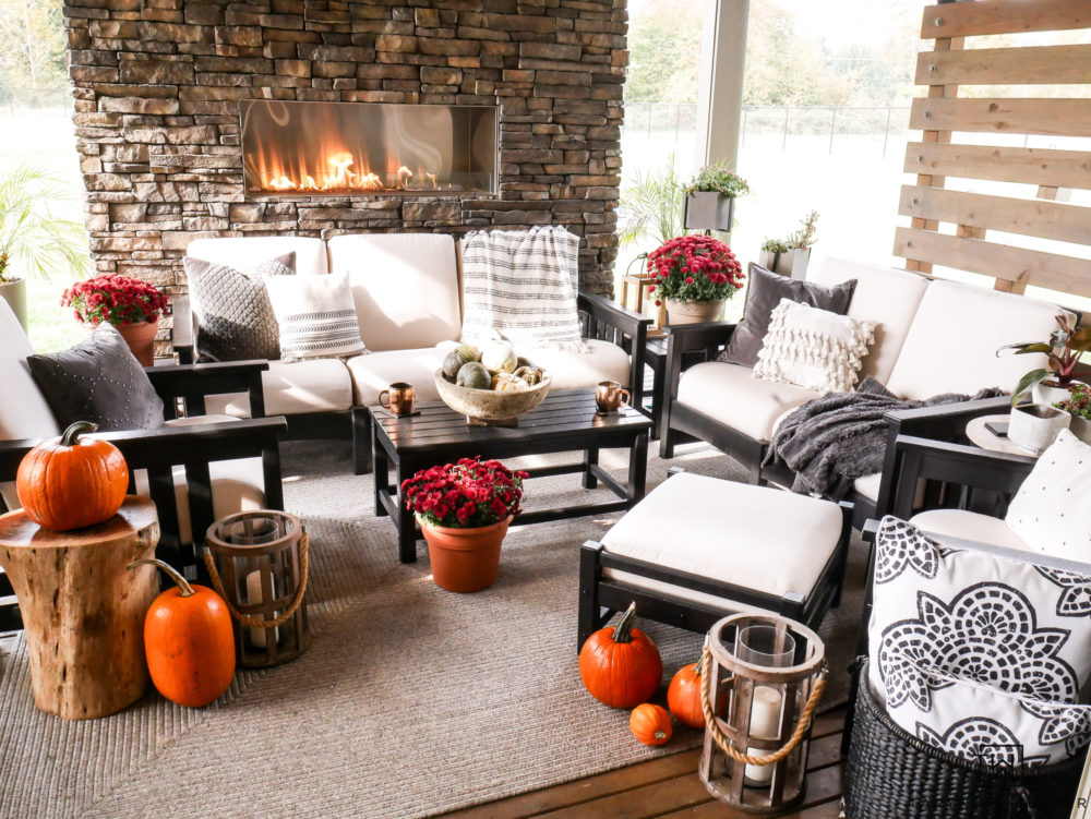 Outdoor living space in the Pacific Northwest with large stone fireplace and cozy seating area.