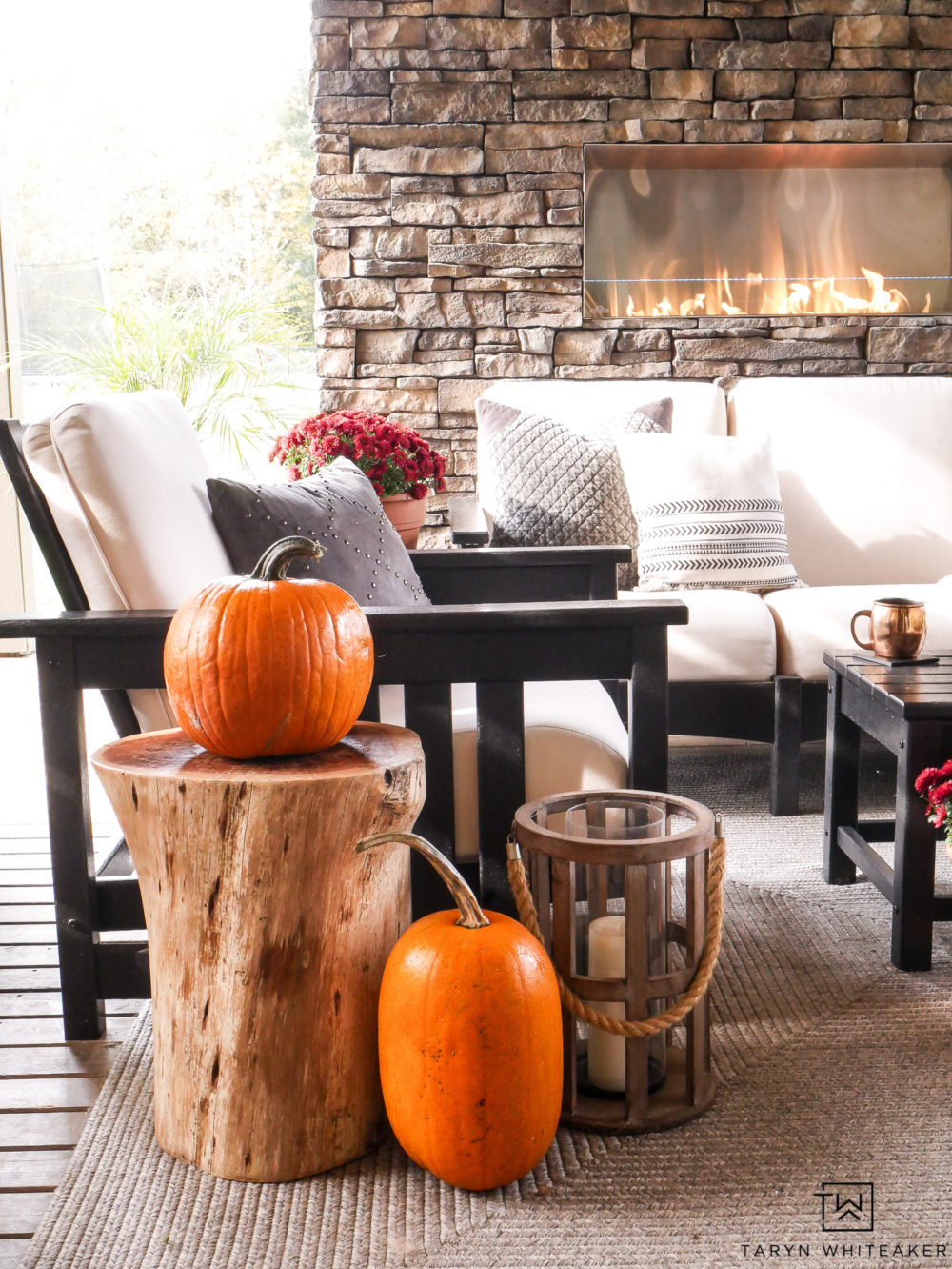Decorating an outdoor living space for fall with pops of orange pumpkins and red mums.