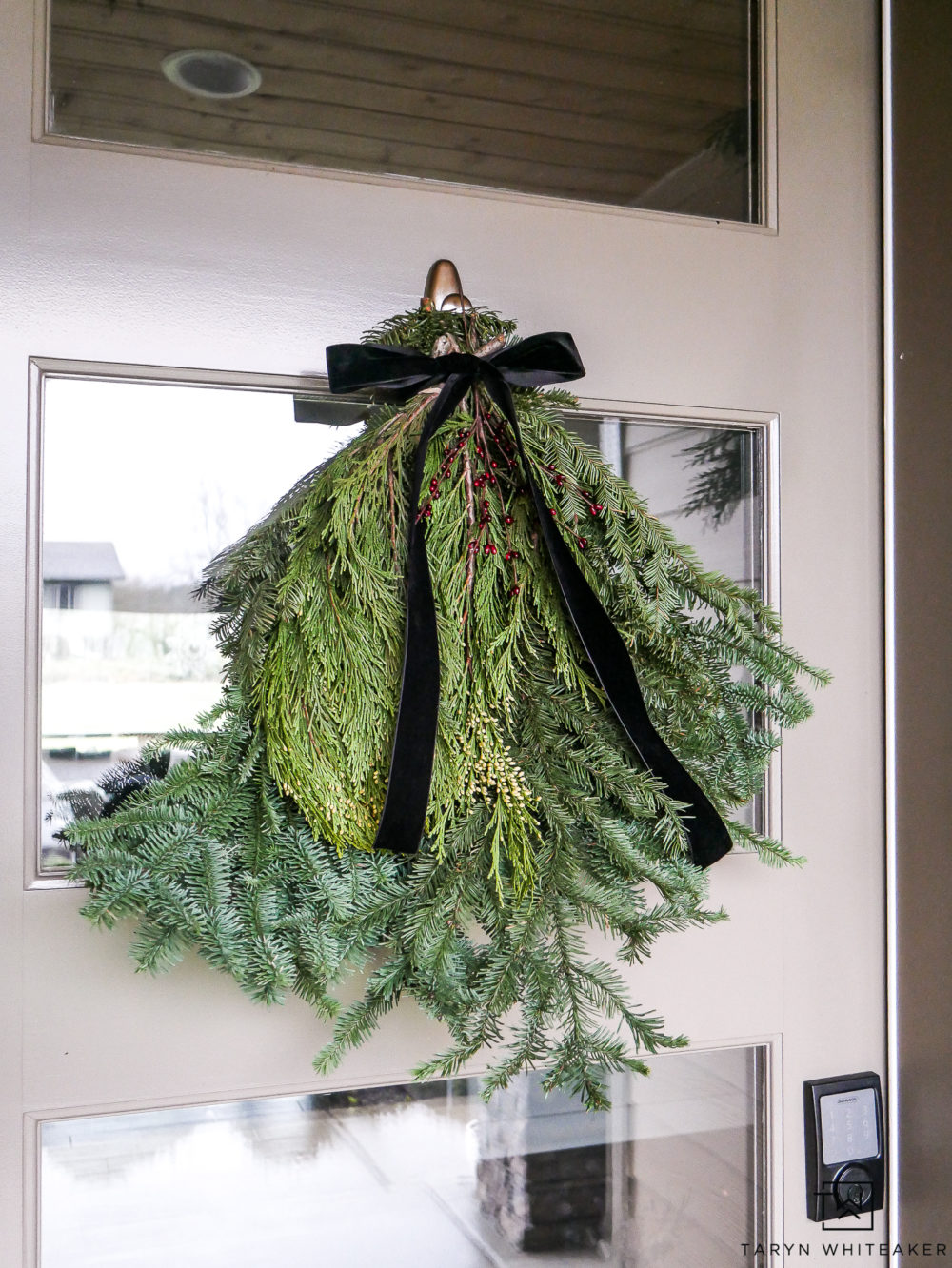 Create your own modern Christmas wreath using a bushel of fresh greens tied up with a simple ribbon.