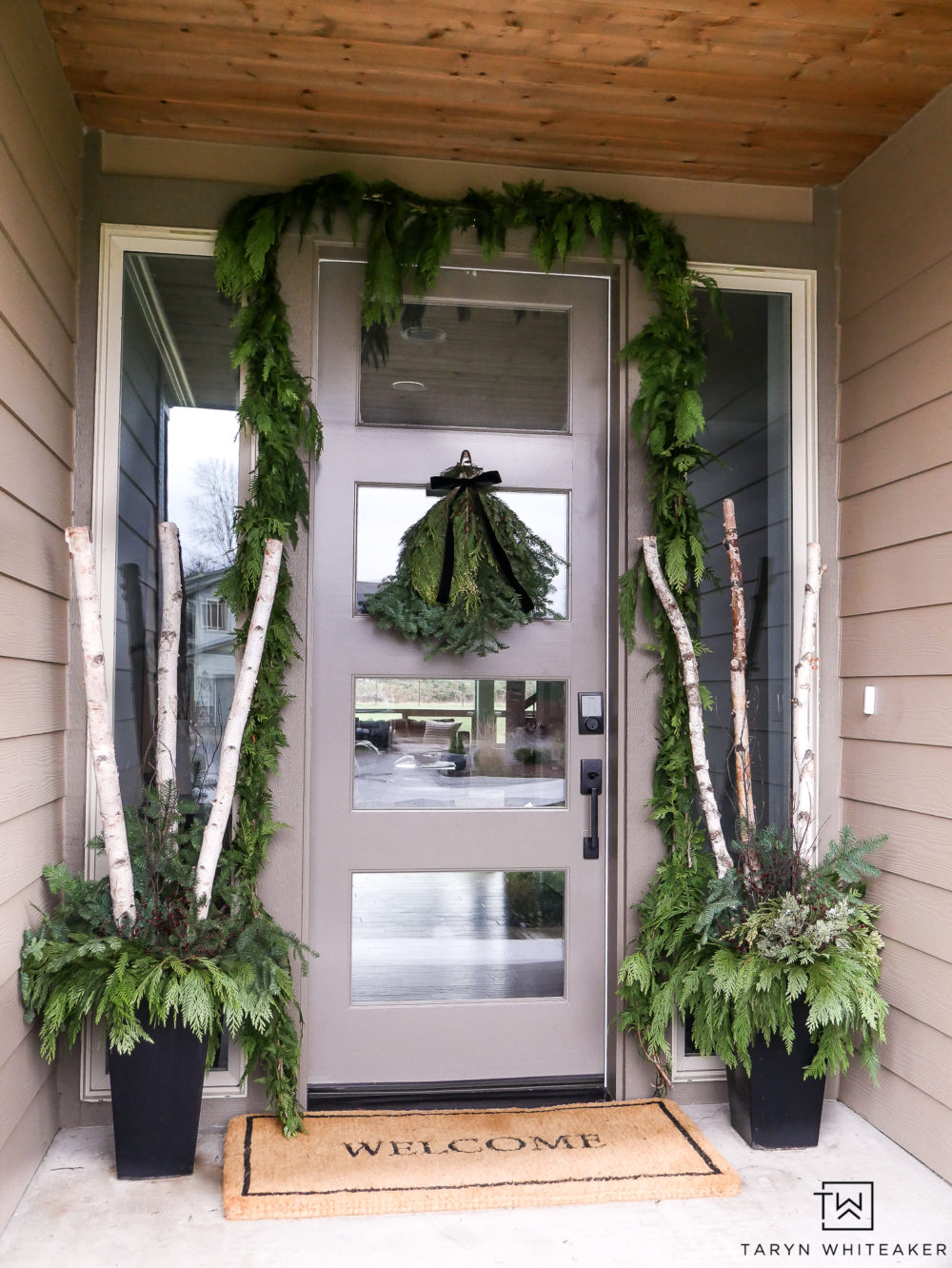 This Christmas Porch With Fresh Greens is both traditional and a little modern. Love the minimalist approach to porch decorations for the holidays.