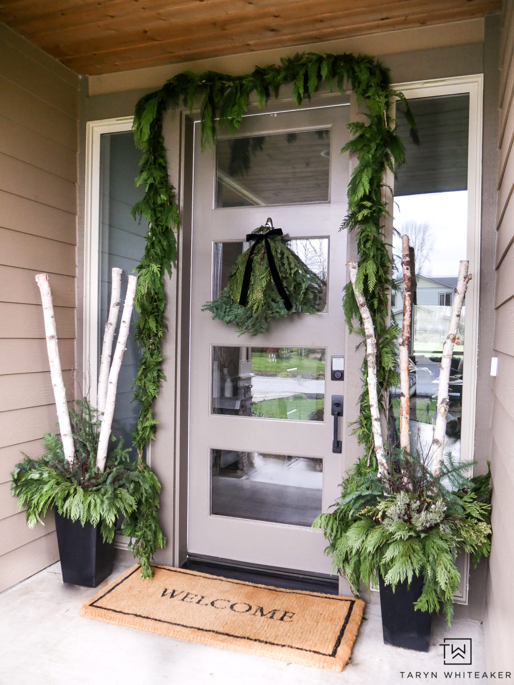 Classic Christmas Porch Decor using fresh green garland around the door and winter planters with birch logs!