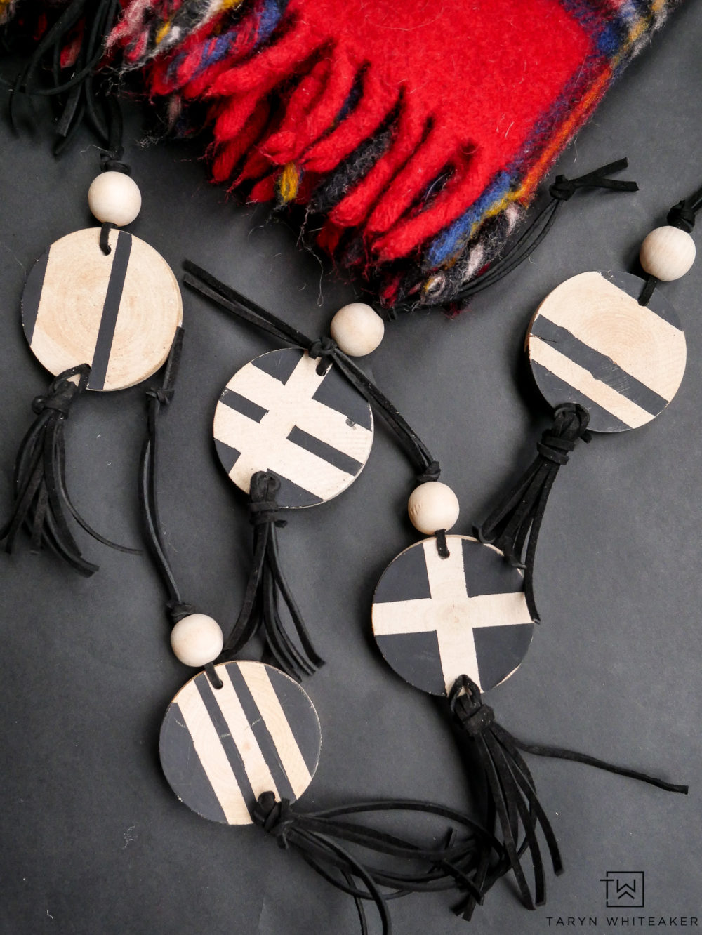 Make these Scandinavian inspired Christmas ornaments using craft wood rounds, black leather cording and wood beads. Such a unique Christmas ornament idea,