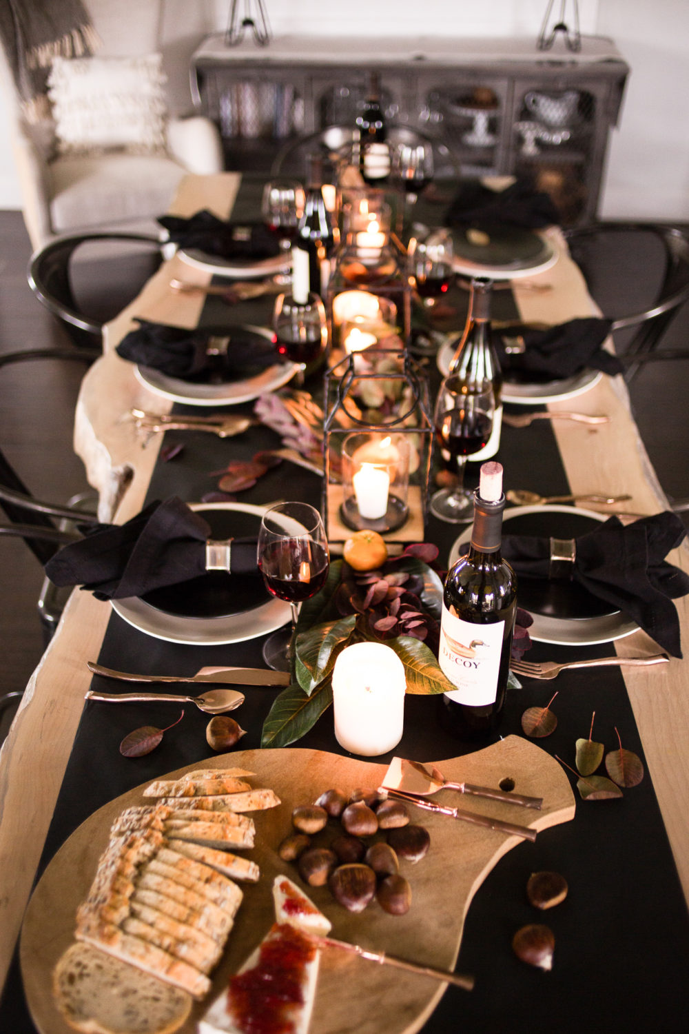 Timeless and classic, dark and moody Thanksgiving tablescape with magnolia leaves and clementine oranges with pops of copper.