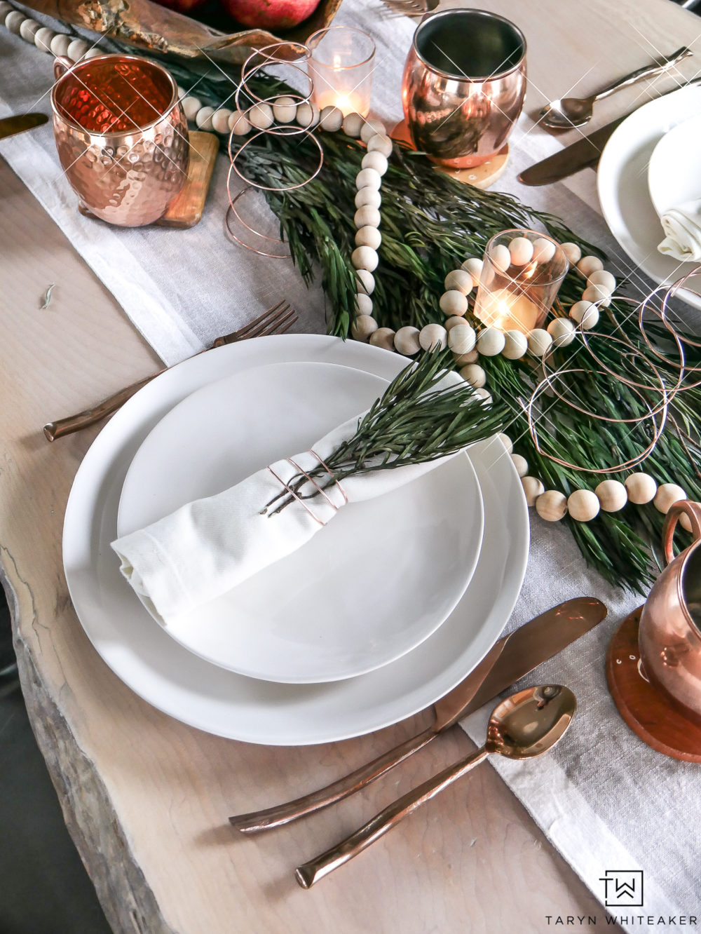 Simple Christmas Table Setting with white plates and fresh greenery.