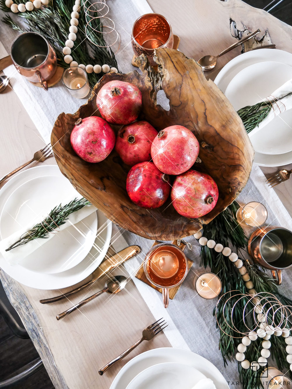 Keep your centerpiece simple by using a unique bowl and filling it with fresh fruit or vegetables that are in season. Love this pomegranate centerpiece mixed with the fresh greens.