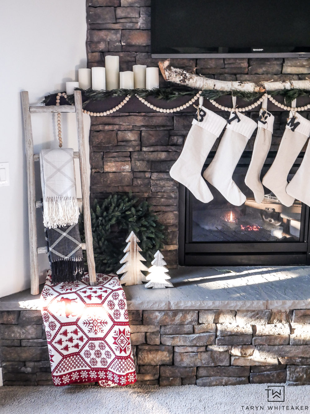 A neutral Christmas mantel with pops of red and green decor. Love the simple white candles and greenery on the mantel along with wood bead garland.
