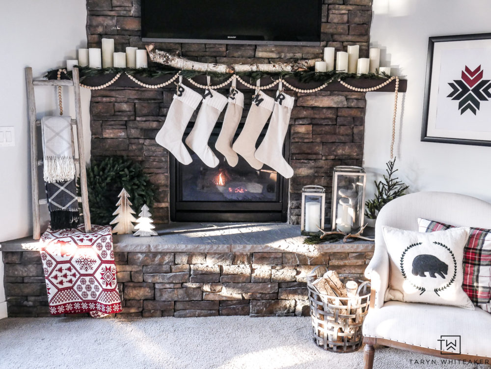 Neutral Christmas mantel on large stone fireplace. Love the subtle pops of red and green and plaid!