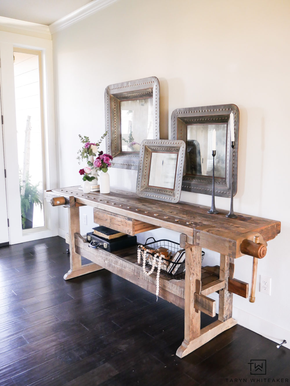 Give a welcoming look to your entry way with.a wood console table decorated with large scale items and soft fresh flowers. Mixing industrial and famine touches is a wonderful contrast.