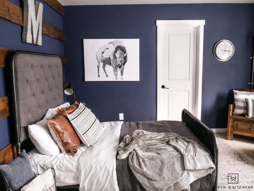 Awesome boy room design using dark navy walls and industrial decor.