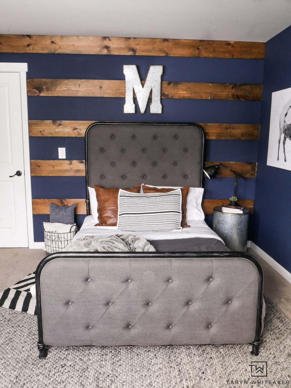 Rustic boy's room with dark navy walls and wood accents. Love the industrial decor and pops of pattern.
