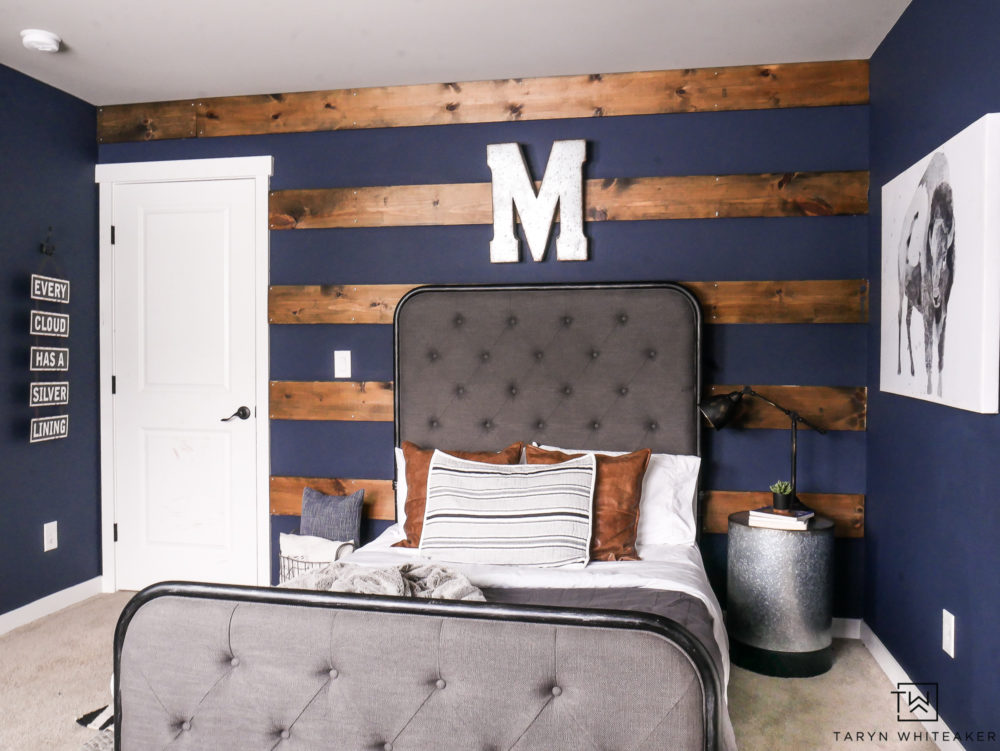 Awesome wood striped wall with dark navy walls behind. Love this rustic boys room with modern farmhouse style.