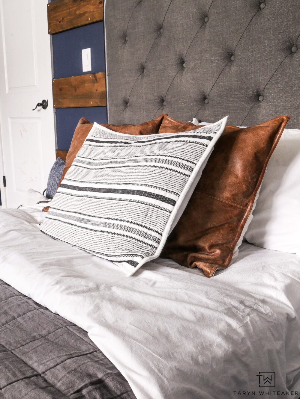 Modern farmhouse bedding with gray duvet, cognac leather pillows and pops of black and white!
