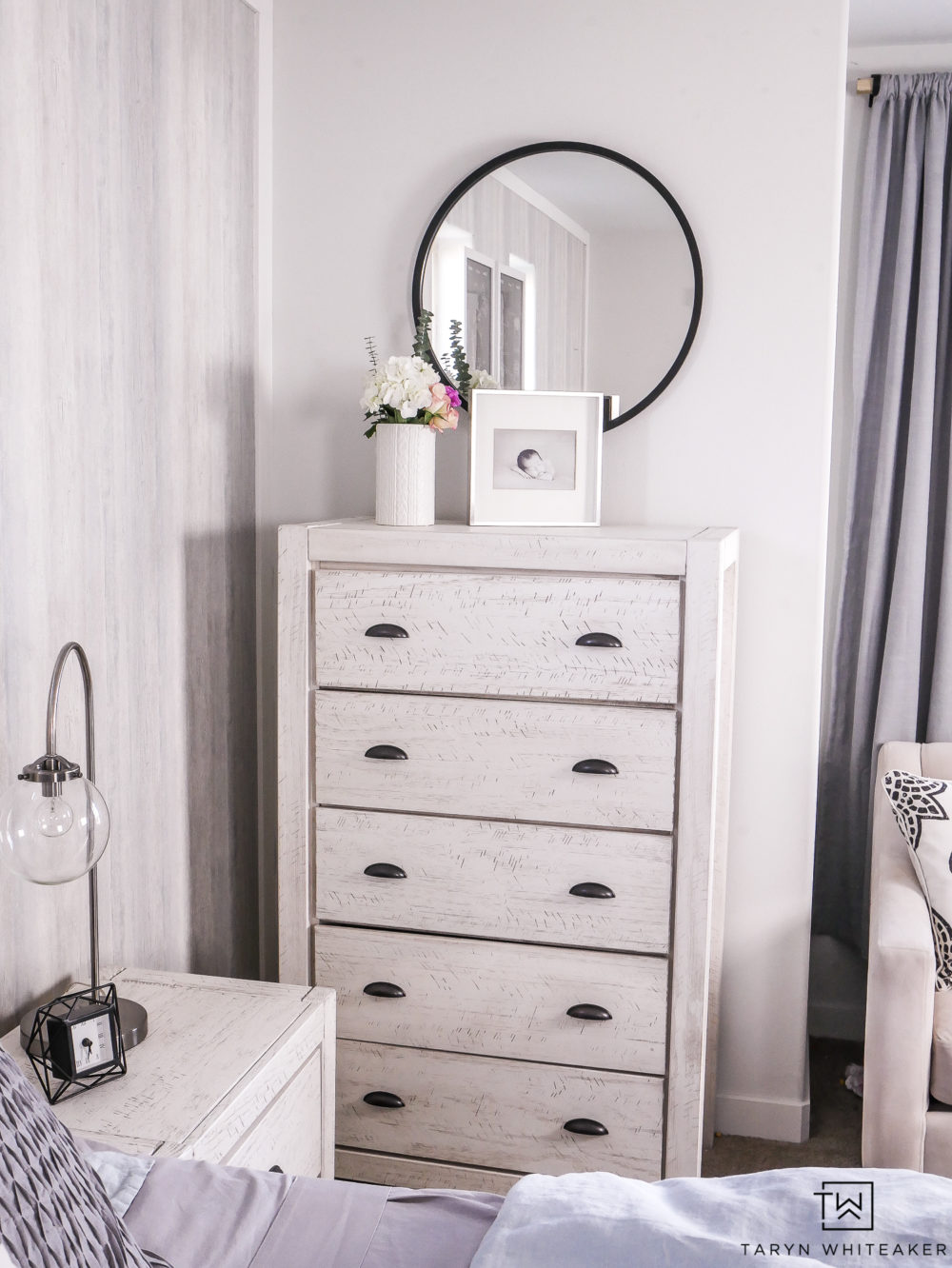 White washed dresser with black modern mirror.