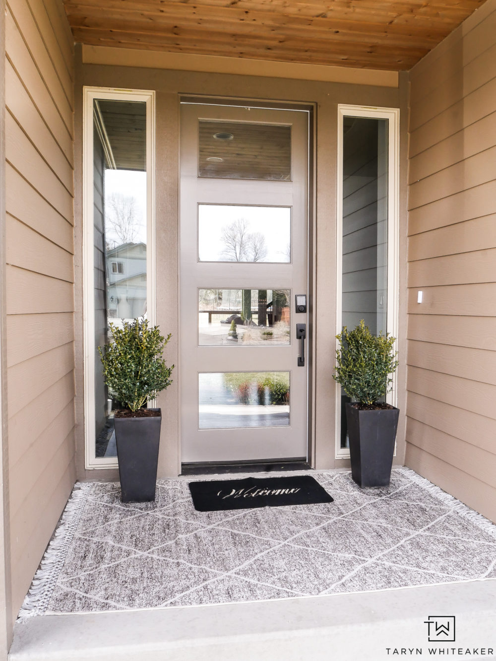 Classic spring porch decor with layered rugs and boxwood planters
