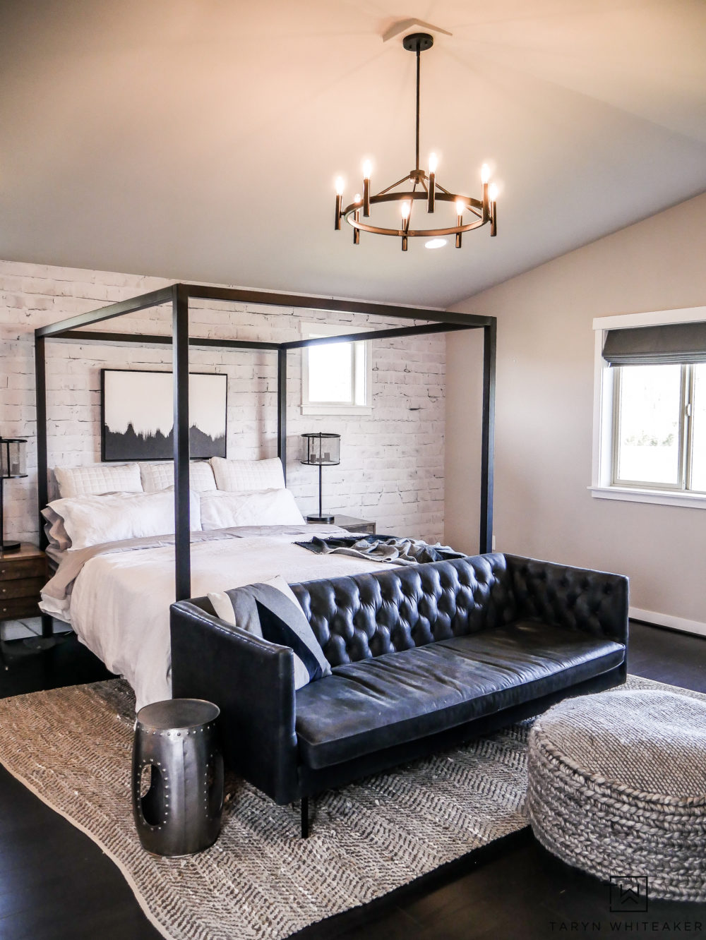 Modern industrial black and white master bedroom design with black hardwoods, canopy bed and black Chesterfield.