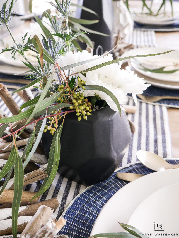 Black vases with modern coastal floral arrangements.