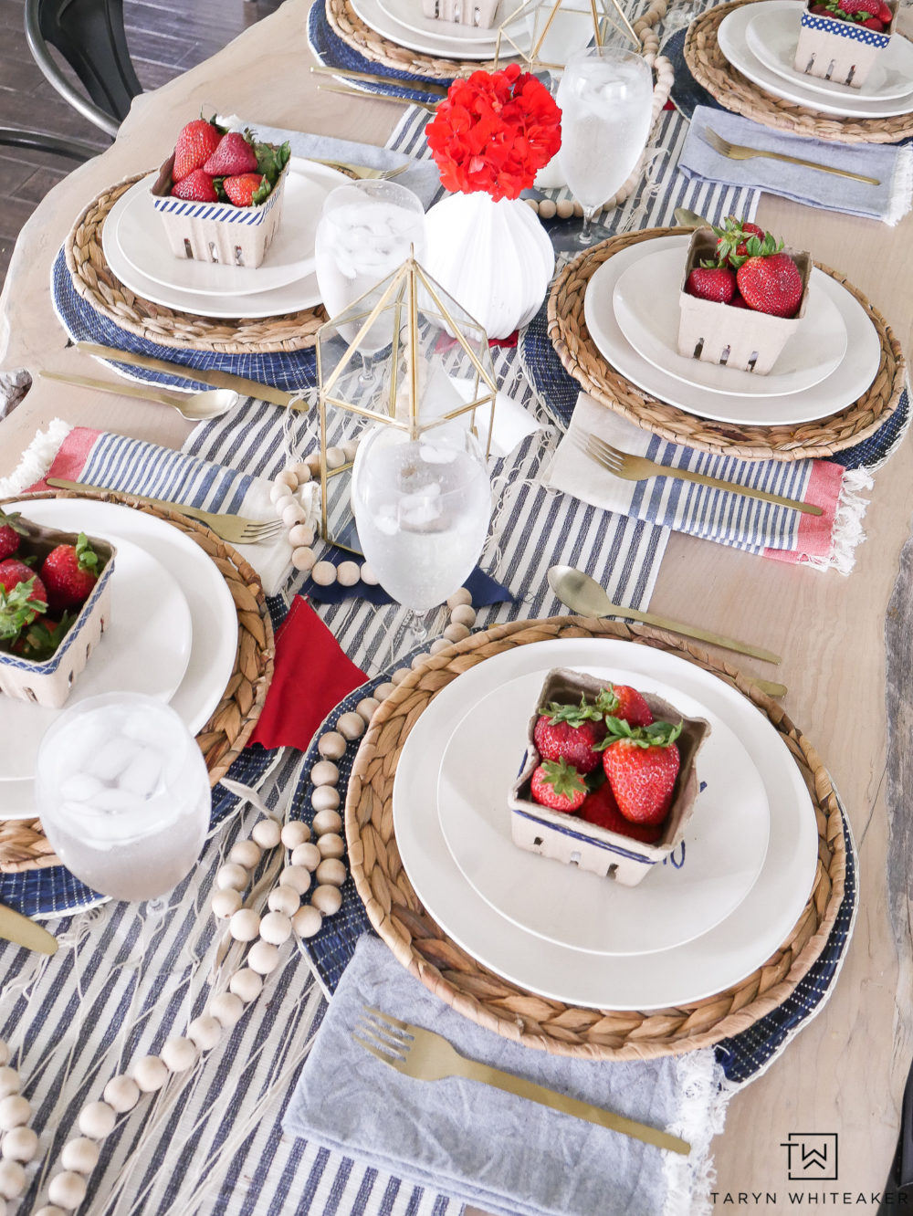 Nautical inspired table setting with gold lanterns, tickling table runner and fresh berries!