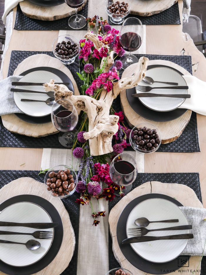 Elegant and modern black and white summer table design mixed with drift wood centerpiece, wood chargers and modern dishes. Love how the purple and pink flowers pop against the neutral decor.