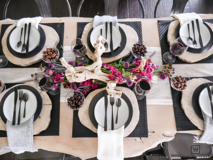 Beautiful rustic modern table design featuring natural elements from drift wood centerpiece with farm fresh flowers and wood charger.