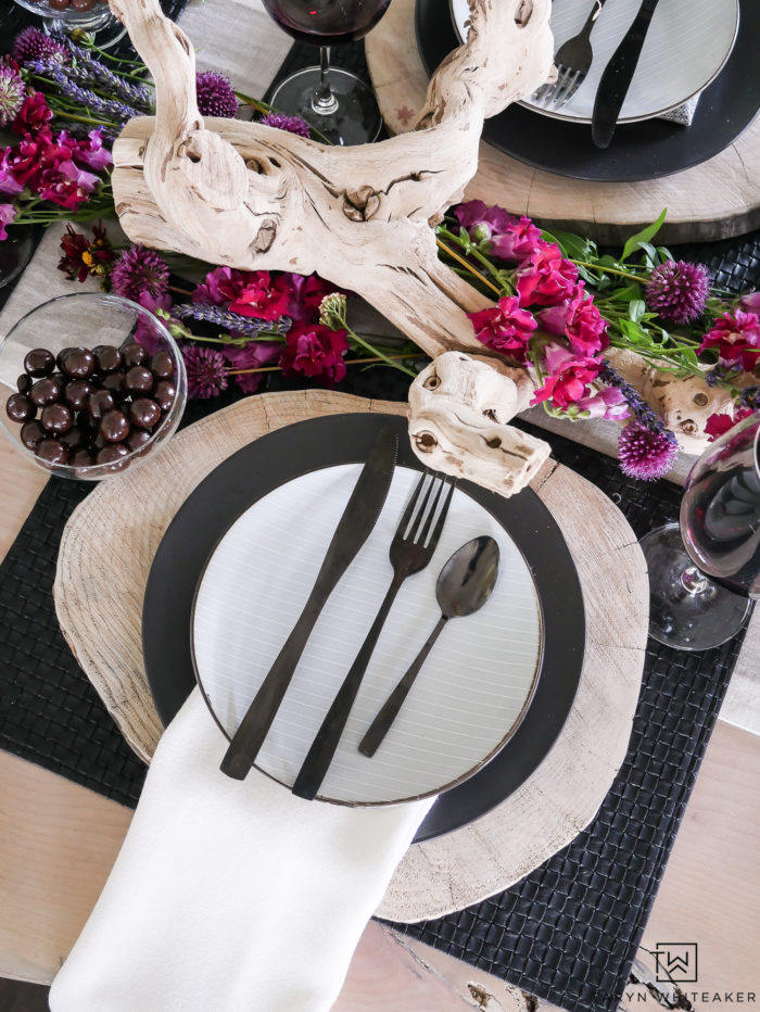 Beautiful black and white rustic modern tablescape with pops of earth tones! Love how the purple and pink flowers look on the centerpiece.