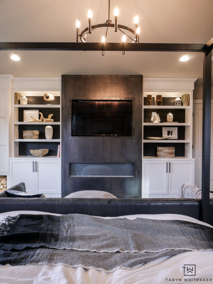 Custom luxe builtins in the master bedroom with a steel fireplace and white builtins with black background. Such a great modern contemporary look for a high end look.