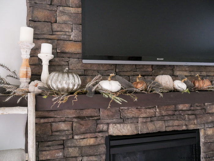 Pumpkins across mantel with greenery and feathers.