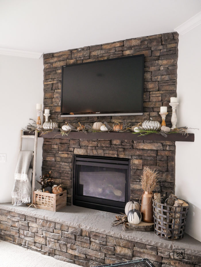 Love this stone fireplace with all the fall colors. Create an elegant and natural fall mantel using neutral colors, pops of copper and natural fall textures. Love the pumpkin mantel display.
