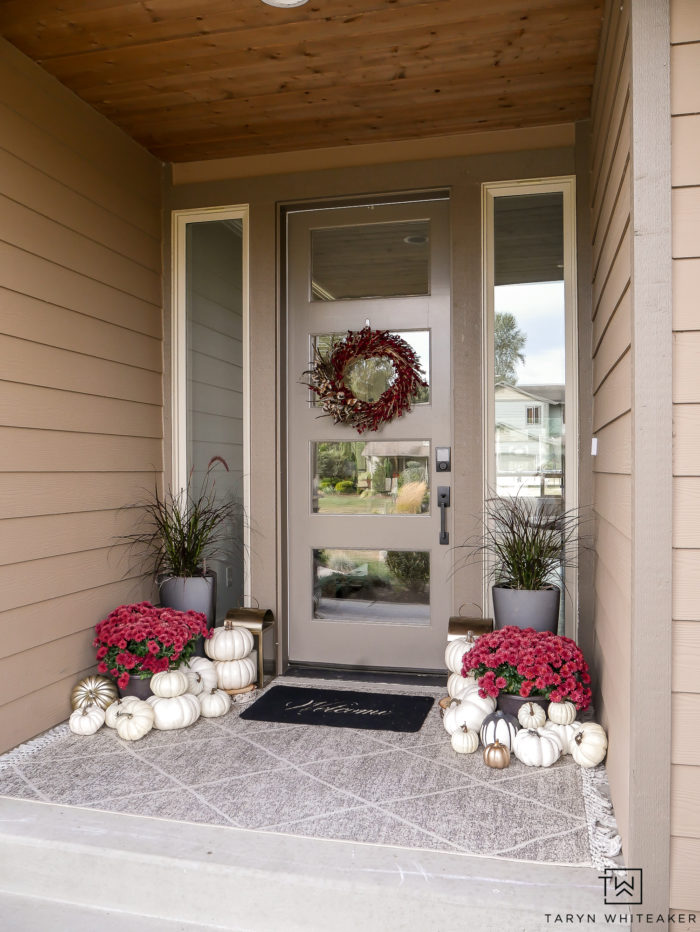 This modern fall porch decor is classic and elegant. The red mums and white pumpkins paired with the black planters gives the proch a bold look for fall.