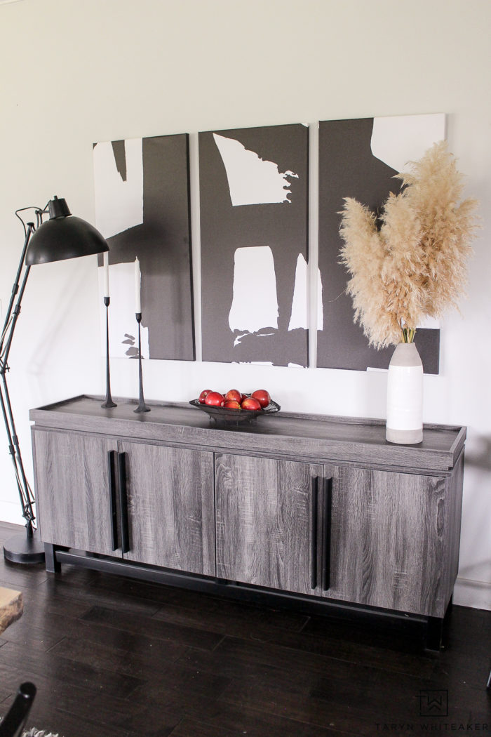 Mid-century modern sideboard display with black and white modern artwork. love the pampas grass accents.