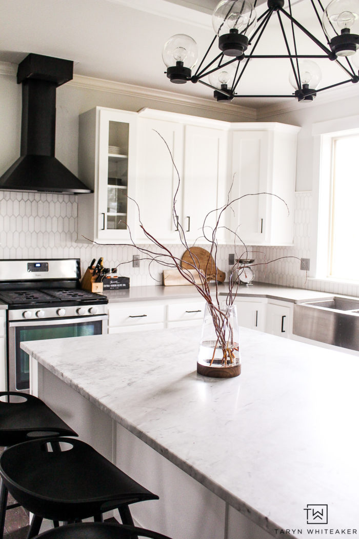 Black and white modern kitchen with black range hood and natural accents.