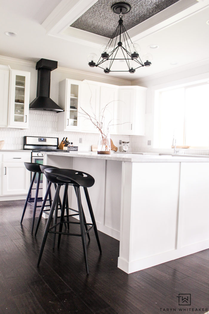White modern Kitchen with black accents and modern black kitchen bar stools.
