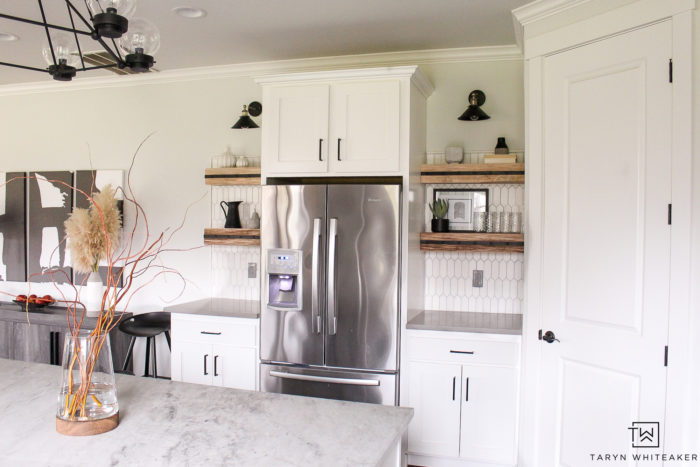Black and White kitchen with floating open shelves and black industrial kitchen sconces.