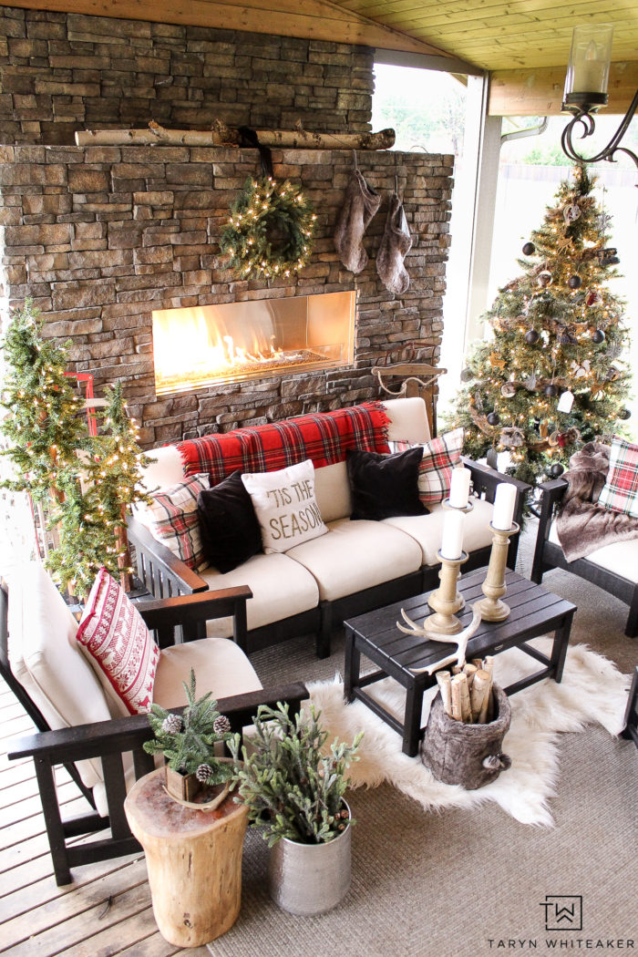 decorate your outdoor patio for Christmas with multiple Christmas trees and tons of Christmas decor for a festive outdoor space for the holidays.