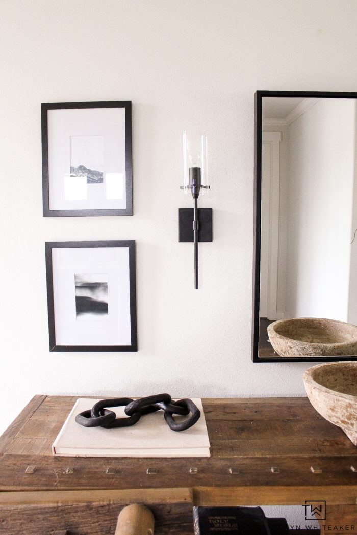 Modern back wall sconces with black pictures and mirror