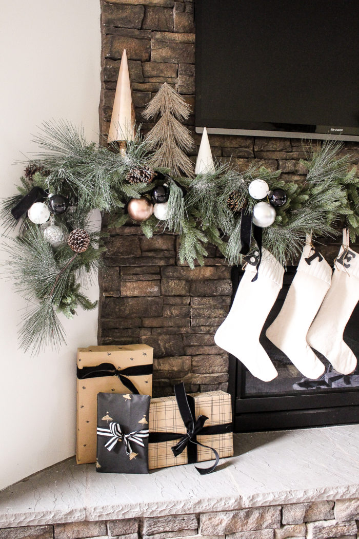 Neutral Christmas mantel using black and white decor with pops of metallic.