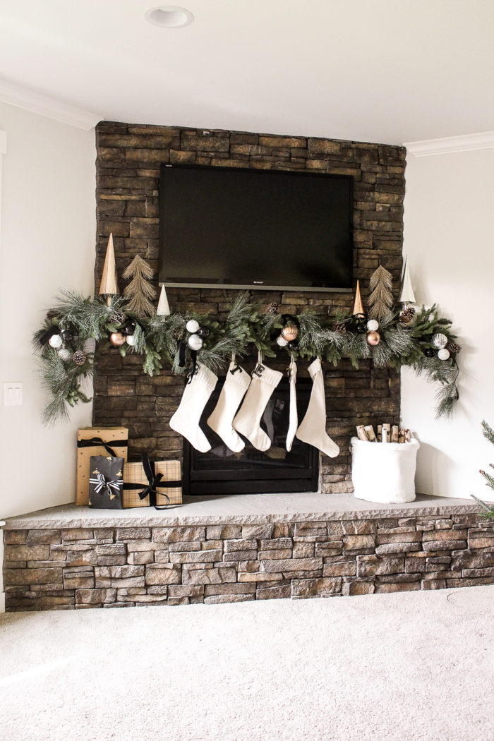 Simple Christmas Mantel using lush greenery over mantel and metallic ornaments tucked throughout.