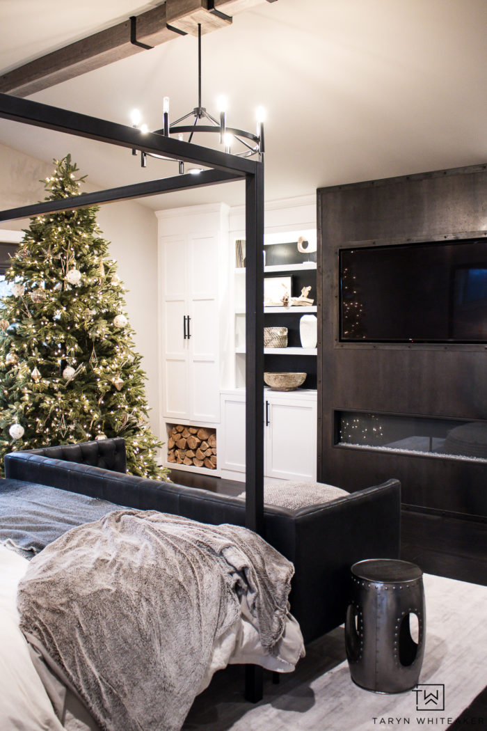 Modern master bedroom decorated for Christmas with a large Christmas tree and rustic accents.