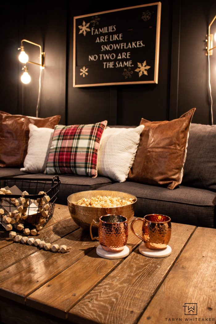 Perfect Movie night at home with moody movie room with dark walls and some cozy plaid decor.