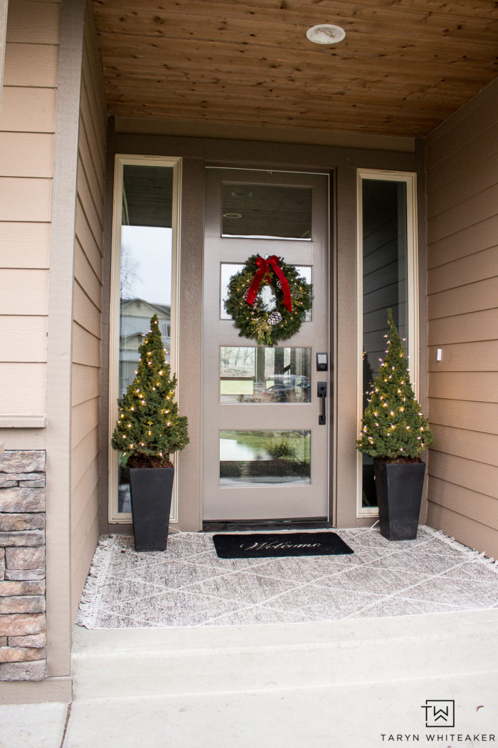 Keep it simple with this Classic Christmas Porch. Featuring layered porch rugs, mini Christmas trees and a fresh green wreath with red bow!