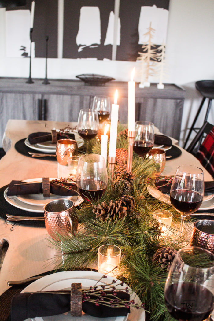 Combine rustic natural elements and a little Christmas glam to create this sleek Rustic Chic Christmas Table with black and white dishes and pops of greens.