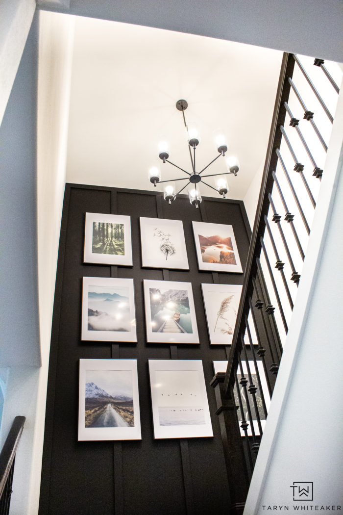 This custom gallery wall took a builder grade staircase into a custom modern look with a bold accent wall and oversized gallery wall.