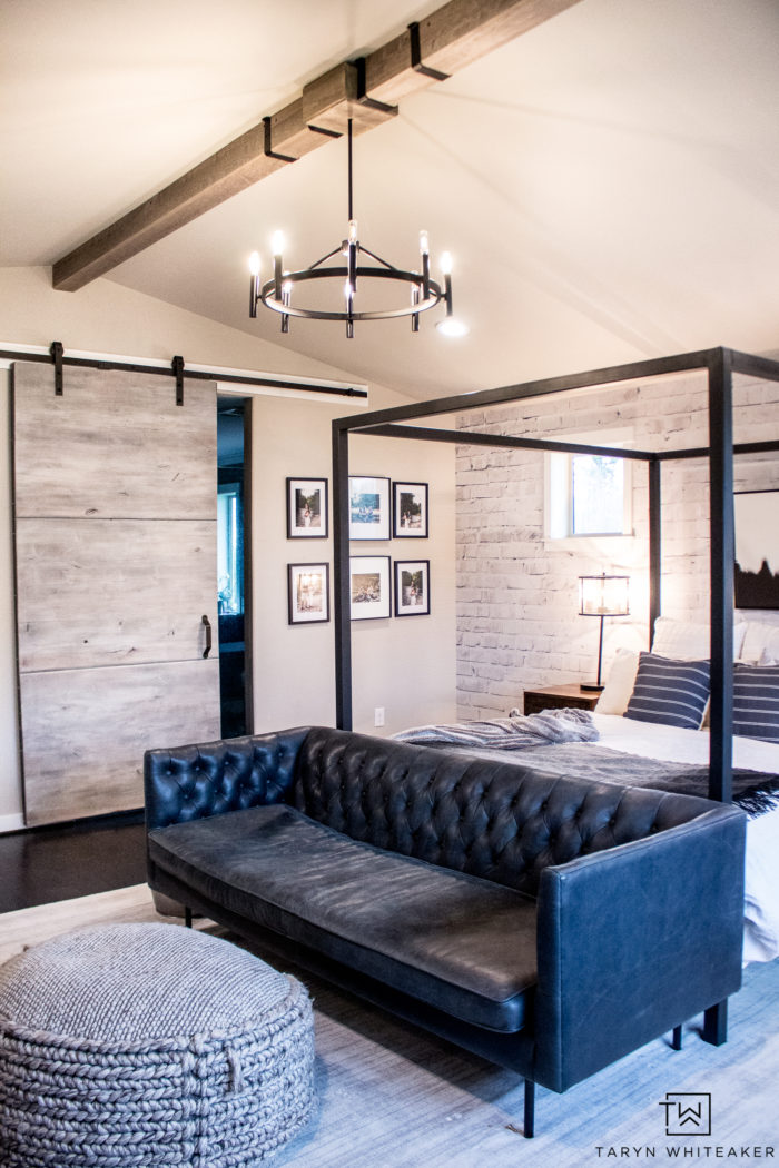 Take a tour of this rustic modern black and white master bedroom filled with wood beams, oversized barn door and tons of texture and clean lines!