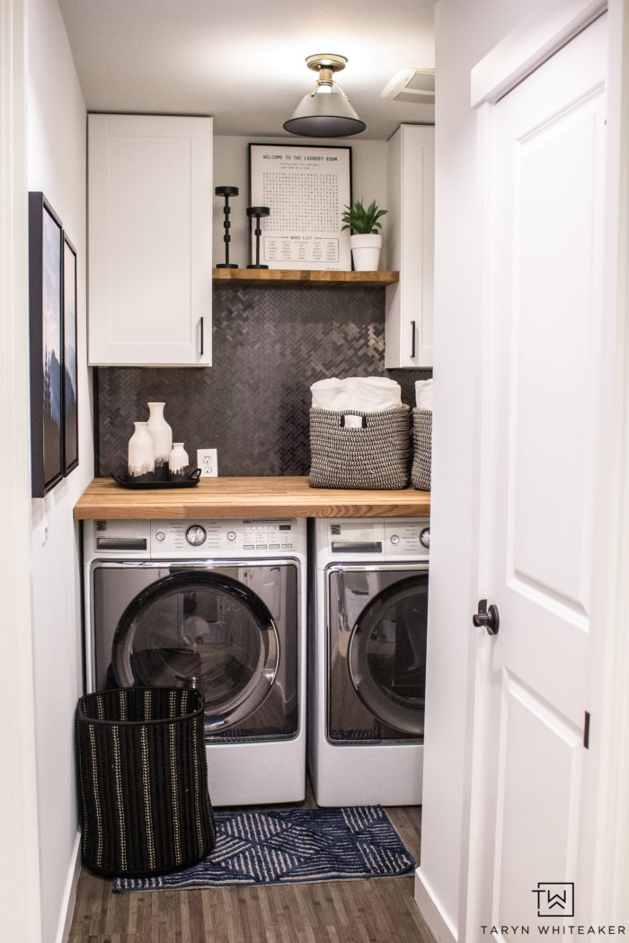 Love this Small Laundry Room Makeover ! The modern black and white laundry room with wood accents looks so chic.