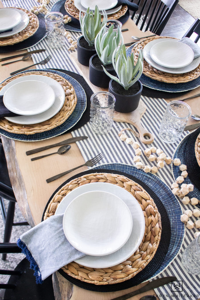 Black and White and navy spring tablescape using a variety of layered place mats and wood tones.
