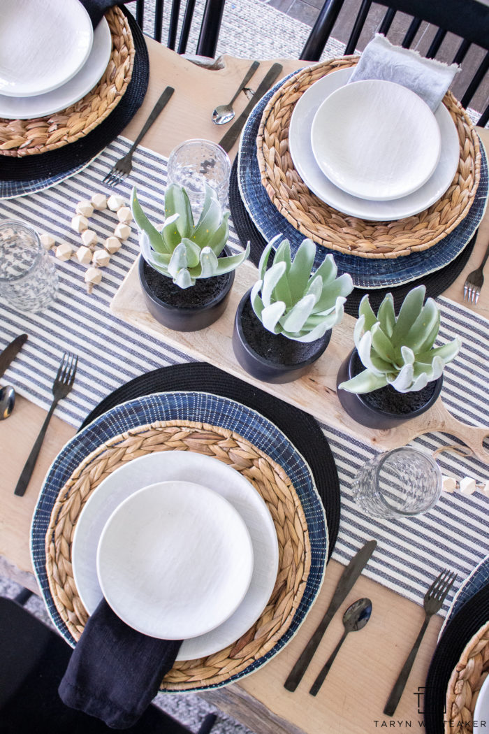 For a simple centerpiece idea, add a small cutting board and place three plants on top!